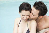 Couple relaxing in pool, man kissing woman's cheek