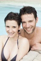 Couple relaxing together in pool, portrait