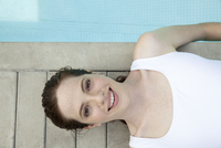 Young woman sunbathing by pool, smiling cheerfully, portrait