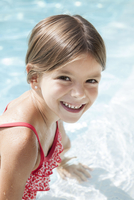 Girl in swimming pool, smiling cheerfully, portrait