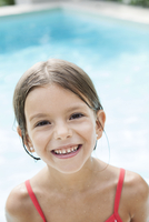 Little girl in swimming pool, smiling cheerfully, portrait