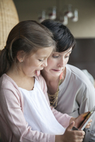 Mother and young daughter using digital tablet and making funny faces 11001062786| 写真素材・ストックフォト・画像・イラスト素材|アマナイメージズ