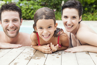 Family relaxing together in pool, portrait
