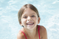 Little girl in pool, smiling cheerfully, portrait