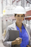 Businesswoman with hard hat in warehouse, portrait