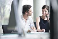Businessman listening to associates phone call 11001062920| 写真素材・ストックフォト・画像・イラスト素材|アマナイメージズ