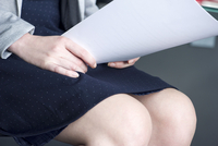 Woman holding paperwork on lap, cropped