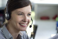 Telemarketer wearing headset, smiling