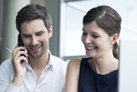 Business colleagues smiling together, man talking on cell phone