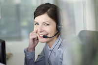 Businesswoman wearing headset during conference call, portrait
