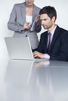 Businessman working on laptop computer, colleague looking over his shoulder