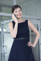 Businesswoman talking on cell phone, smiling cheerfully