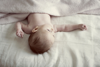 Newborn baby lying on bed