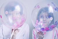 Children hiding behind transparent balloons