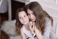 Girl embracing younger sister, portrait