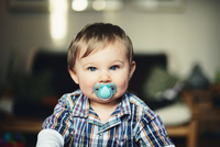 Baby boy with pacifier in his mouth, portrait