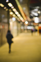 Pedestrian walking on sidewalk at night, defocused