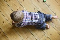 Baby boy crawling on floor, overhead view