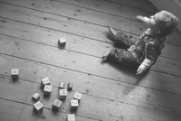 Baby boy sitting on nursery floor with wooden blocks 11001063176| 写真素材・ストックフォト・画像・イラスト素材|アマナイメージズ