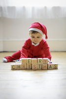 """Baby boy dressed as Santa Claus with toy blocks reading Merry Christmas"""""""