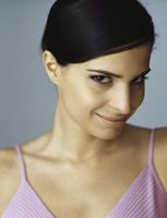 Woman smiling slyly at camera, portrait