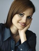 Woman holding head, smiling, portrait