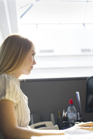 Young woman working intently in office cubicle