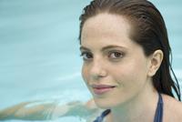 Woman soaking in swimming pool, portrait