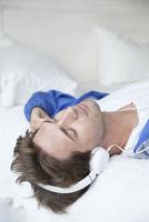 Man wearing headphones lying on back