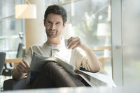 Man relaxing with newspaper and cup of coffee
