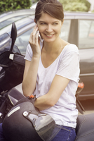 Woman sitting on parked motorcyle, talking on cell phone