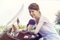 Woman leaning against motorcycle, using smartphone 11001063420| 写真素材・ストックフォト・画像・イラスト素材|アマナイメージズ
