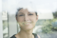 Woman looking through window, smiling, portrait