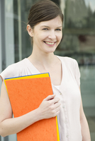 Woman carrying folders, smiling cheerfully, portrait