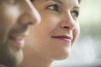 Close-up of couple smiling, focus on woman