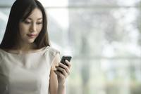 Businesswoman using smartphone 11001063585| 写真素材・ストックフォト・画像・イラスト素材|アマナイメージズ