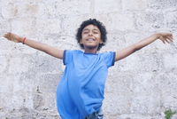 Boy standing with his arms outstretched, eyes closed, portrait