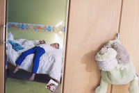 Boy daydreaming on bed, reflected in bedroom mirror