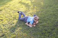 Boys wrestling on lawn