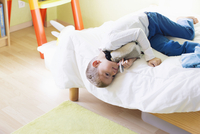 Boy lying on bed with stuffed toy