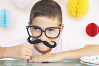 Boy wearing fake glasses and mustache at a birthday party, portrait