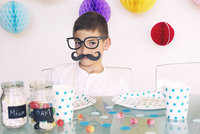 Boy wearing fake glasses and mustache at a birthday party