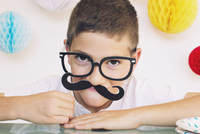 Boy wearing fake mustache and glasses at a birthday party