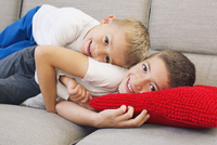 Young brothers lying together on sofa