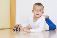 Boy lying on floor playing with toy truck