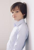 Boy leaning against wall, portrait