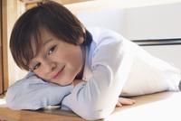Boy resting head on arms, smiling, portrait