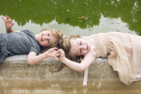 Young sisters lying down on beside pond,holding hands