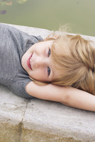 Little girl lying beside pond, portrait