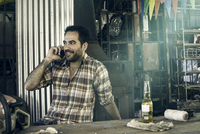 Man having beer and chatting on phone in workshop